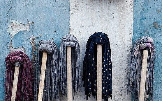 five mops on a wall